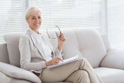 mental health professional holding eyeglasses sitting on sofa smiling